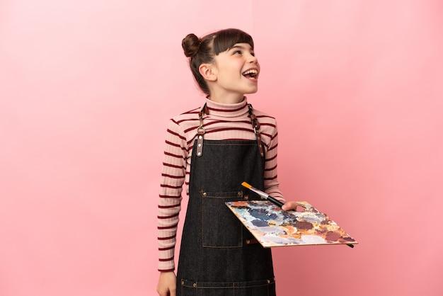 Mała dziewczynka artysta trzymając paletę na białym tle na różowej ścianie, śmiejąc się