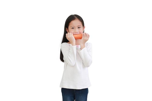 Mała dziewczynka azjatyckich gospodarstwa marchew i gest jedzenie na białym tle. koncepcja dzieci i warzyw
