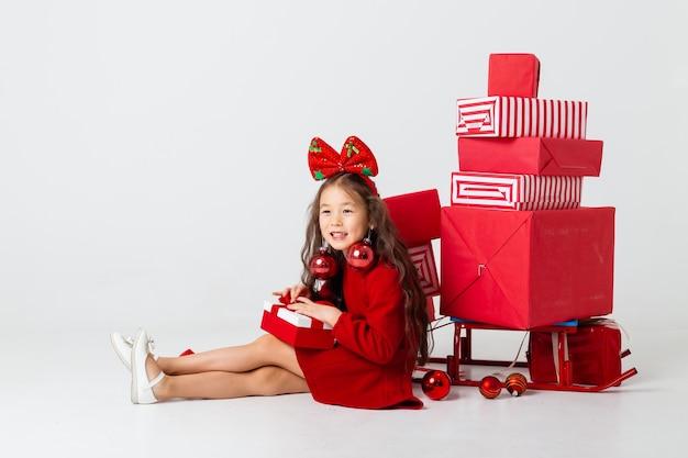 Mała dziewczynka azjatyckich siedzi w czerwonej sukience siedzi z pudełkami na białym tle. koncepcja bożego narodzenia, miejsca na tekst