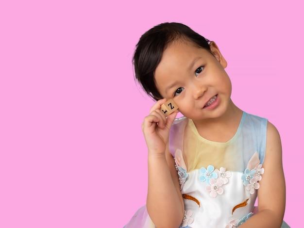 Mała dziewczynka azjatyckich trzyma w ręku blok alfabetu i uśmiecha się