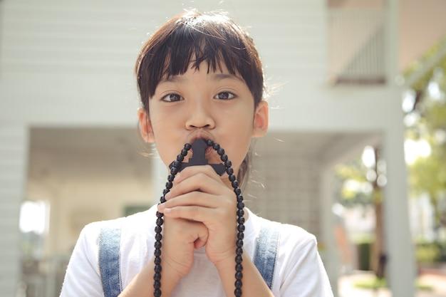 Mała dziewczynka azji modli się trzymając krzyż, koncepcja chrześcijańska.