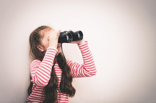 Mała dziewczynka badacz patrzy przez lornetkę