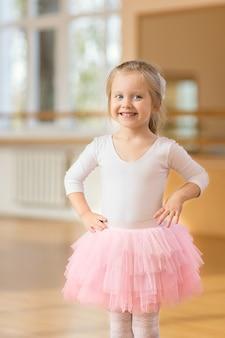Mała dziewczynka baleriny stojącej w pobliżu lustra na siłowni