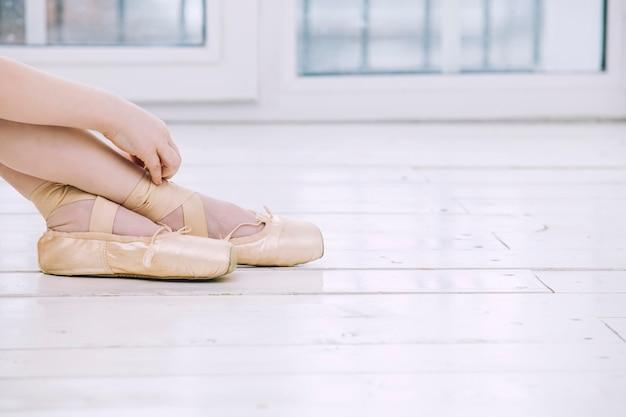 Mała dziewczynka baleriny ubiera buty pointe w jasnym pokoju na szczęśliwe i słodkie