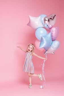 Mała dziewczynka bawi się balonami na różowej powierzchni
