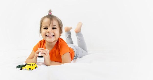 Mała dziewczynka bawi się białym autko. siedząc na białym prześcieradle. uśmiechnięty. dzieci w wieku przedszkolnym.