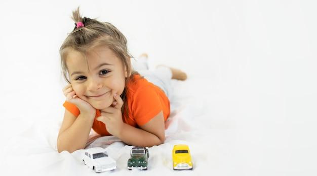Mała dziewczynka bawi się białym autko. układanie na białym prześcieradle. uśmiechnięty.