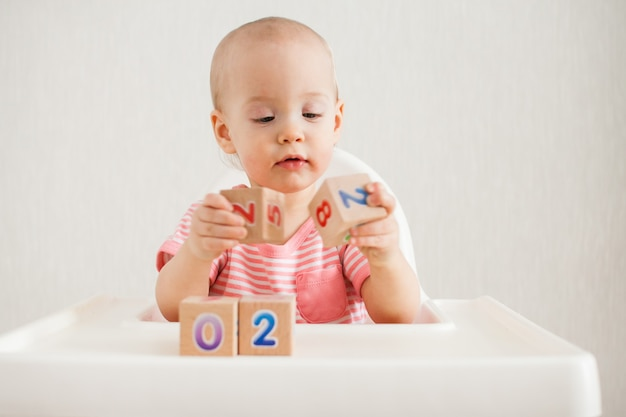 Mała dziewczynka bawi się drewnianymi kostkami z jasnymi numerami 2022