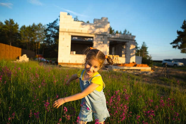 Mała dziewczynka bawi się i tańczy w pobliżu placu budowy swojego przyszłego domu na wsi. czekam na przeprowadzkę, marzenia o przyszłym mieszkaniu. kredyt hipoteczny, kredyt budowlany.
