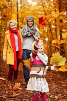 Mała dziewczynka bawi się jesiennymi liśćmi