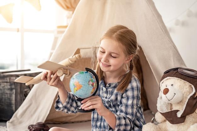 Mała dziewczynka bawi się kulą ziemską i drewniany samolot siedzi w pobliżu wigwamu w pokoju dla dzieci