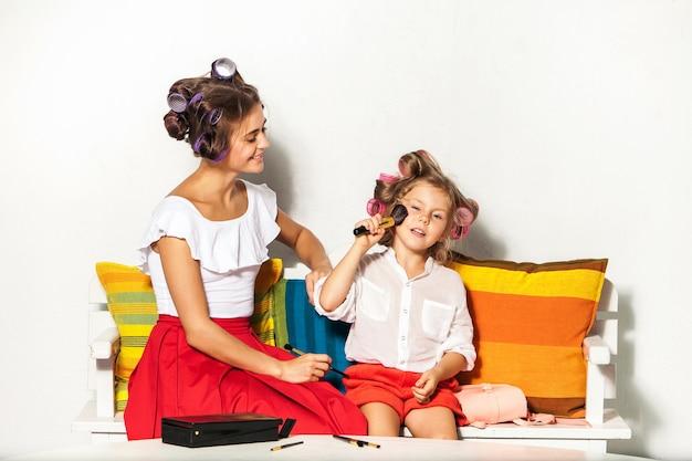 Mała dziewczynka bawi się makijażem swojej mamy na białym tle