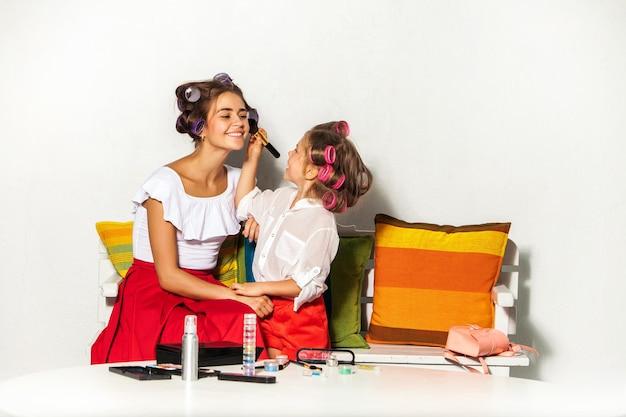 Mała dziewczynka bawi się makijażem swojej mamy