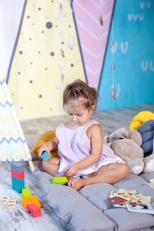 Mała dziewczynka bawi się na podłodze z kolorowych kostek. dziecko bawi się zabawkami w pokoju dziecięcym. mała dziewczynka gra w przedszkolu. koncepcja dzieciństwa, rozwój dziecka. szczęśliwe dziecko bawi się z bloków.