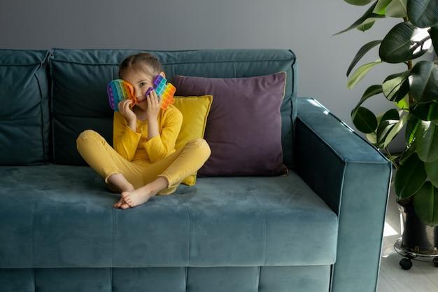 Mała dziewczynka bawi się nowoczesną zabawką pop it siedzącą na kanapie z żółtą poduszką