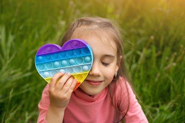 Mała dziewczynka bawi się nowoczesną zabawką pop it w kształcie serca