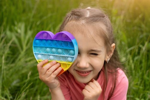 Mała dziewczynka bawi się nowoczesną zabawką popit w kształcie serca