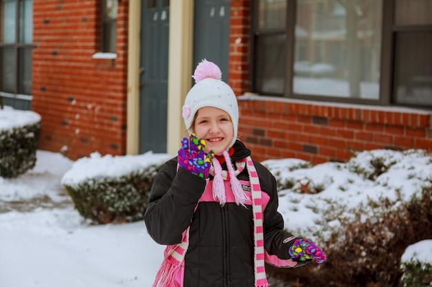 Mała dziewczynka bawi się śniegiem w słoneczny dzień. śmieszna mała dziewczynka zabawy w pięknym winter park. dziecko w zimie. dzieci na zewnątrz. szczęśliwa dziewczyna na śniegu. stonowany obraz.