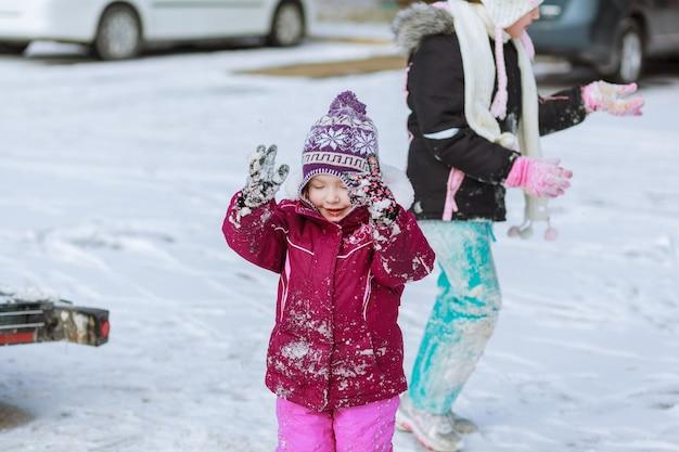 Mała dziewczynka bawi się śniegiem w zimie, zajęcia dla dzieci