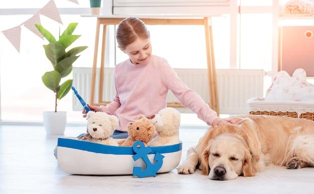 Mała dziewczynka bawi się statkiem morskim i głaszcze psa rasy golden retriever śpiącego obok niej