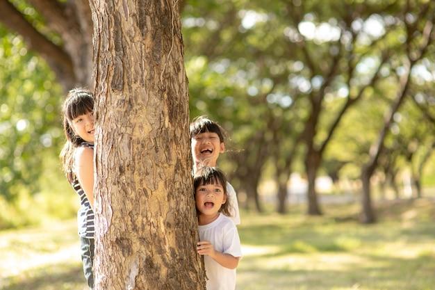 Mała dziewczynka bawi się w chowanego chowając twarz w parku