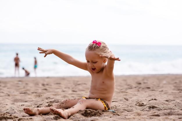 Mała dziewczynka bawi się w piasku nad morzem.
