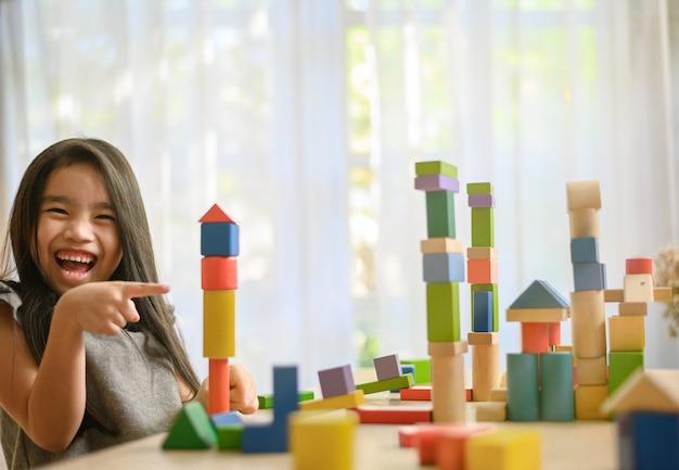 Mała dziewczynka bawi się z bloków budowlanych zabawki budowanie wieży