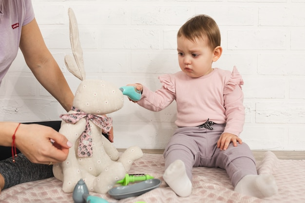 Mała dziewczynka bawi się z mamą jako rodzina lekarza i koncepcja czasu wolnego w domu