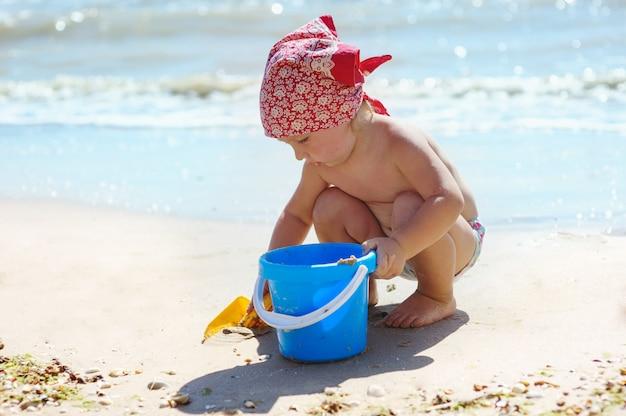 Mała dziewczynka bawi się z niebieskim wiadrem nad morzem