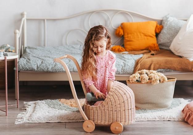 Mała dziewczynka bawi się zabawkami na podłodze w sypialni dla dzieci