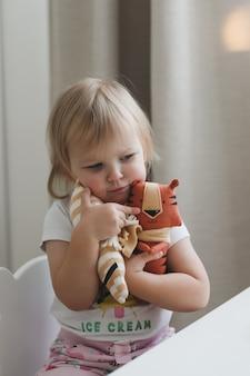 Mała dziewczynka bawi się zabawnym małym tygrysem, symbolem nowości w słonecznym pokoju dziecinnym