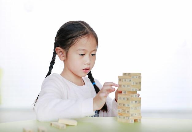 Mała dziewczynka bawić się drewnianą blokową wieżę dla mózg i umiejętności rozwoju fizycznego