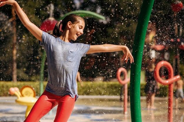 Mała dziewczynka bawić się plamami na wodnym placu zabaw w parku latem. wypoczynek dla dzieci w aquaparku