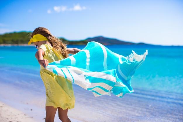 Mała dziewczynka bawić się ręcznikiem plażowym podczas tropikalnych wakacji