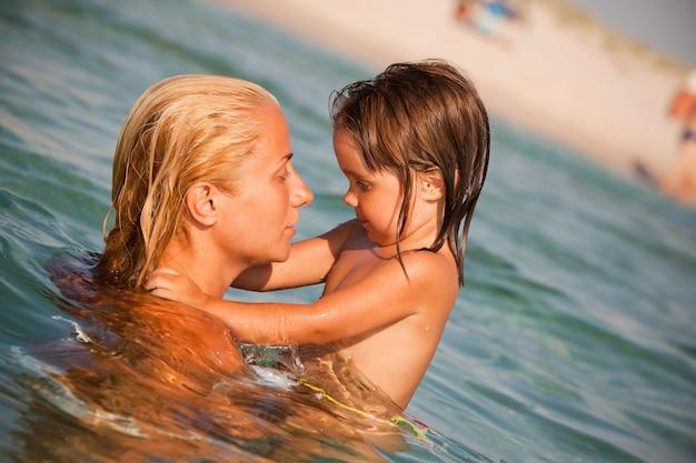 Mała dziewczynka bawić się szyję w morzu i wiesza na morzu