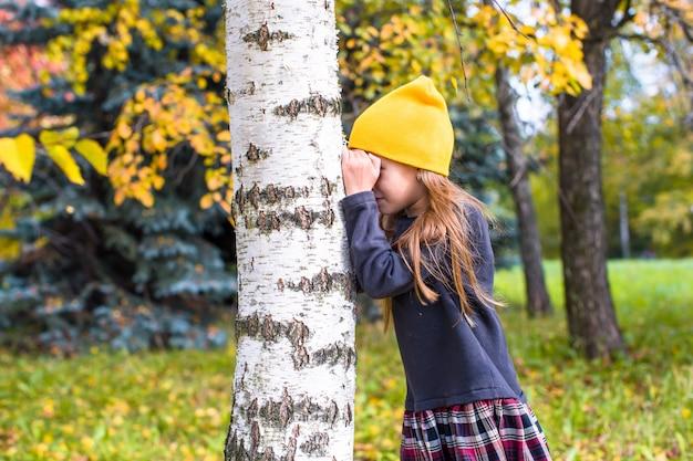 Mała dziewczynka bawić się w chowanego w jesień lesie outdoors