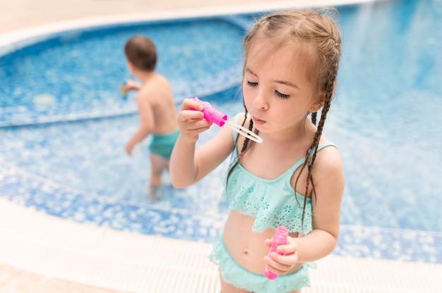 Mała dziewczynka bawić się z bąbel dmuchawą