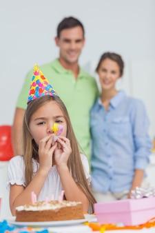 Mała dziewczynka bawić się z partyjnym rogiem