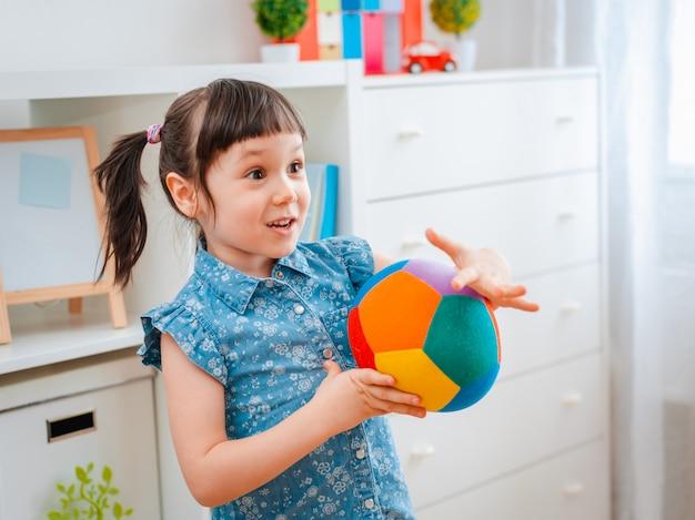 Mała dziewczynka bawić się z piłką w playroom.