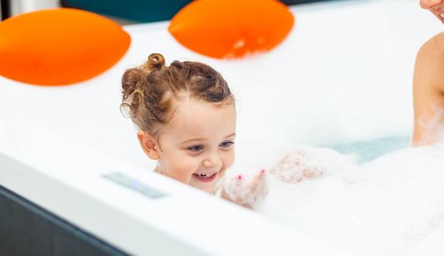 Mała dziewczynka bierze kąpiel w wannie z hydromasażem.