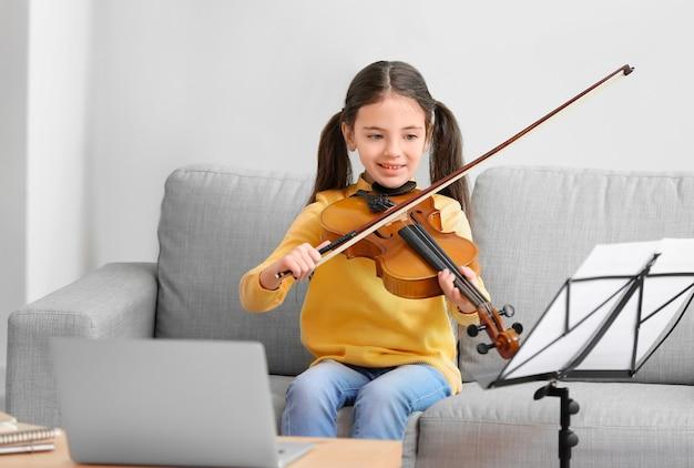 Mała dziewczynka bierze lekcje muzyki online w domu