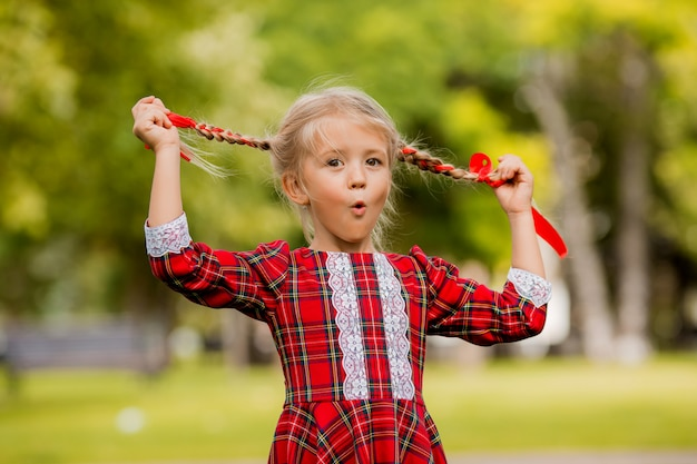Mała dziewczynka blondynka pierwszej klasy czerwona kratka sukienka uśmiechając się na ulicy
