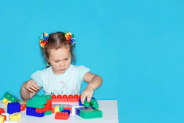 Mała dziewczynka buduje z konstruktorem