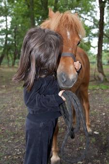 Mała dziewczynka całuje i jej rasowego kucyka szetlandzkiego