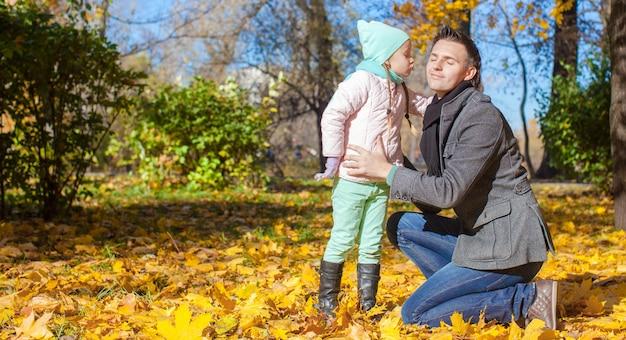 Mała dziewczynka całuje jej ojca w jesień parku