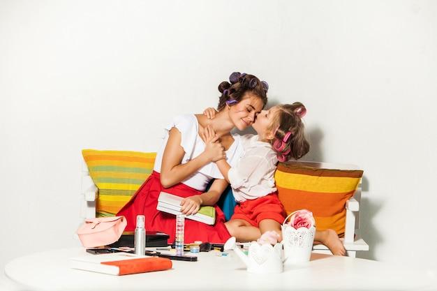Mała dziewczynka całuje matkę na białym tle