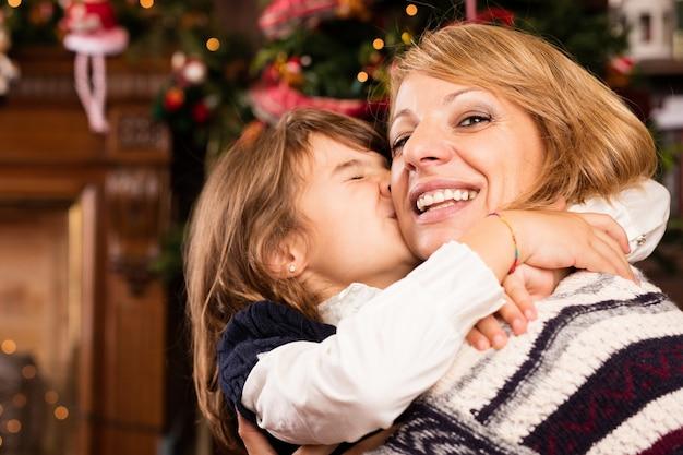 Mała dziewczynka całuje matkę w twarz