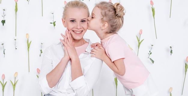Mała dziewczynka całuje szczęśliwej matki