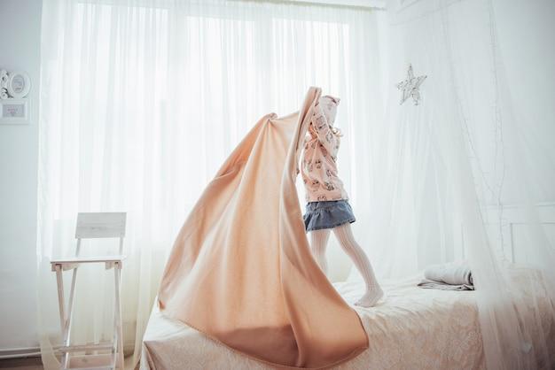 Mała dziewczynka chce owinąć się kocem w świetle sypialni