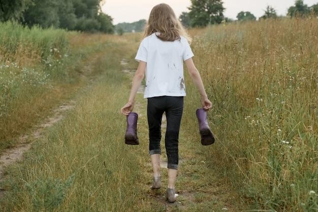 Mała dziewczynka chodzenie na wiejskiej drodze z kalosze w ręce